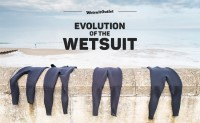 Wetsuits hanging on a sea wall